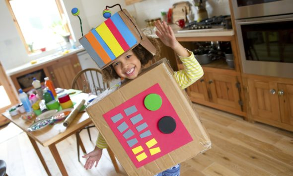Little girl dressed up as a robot using cardboard boxes.